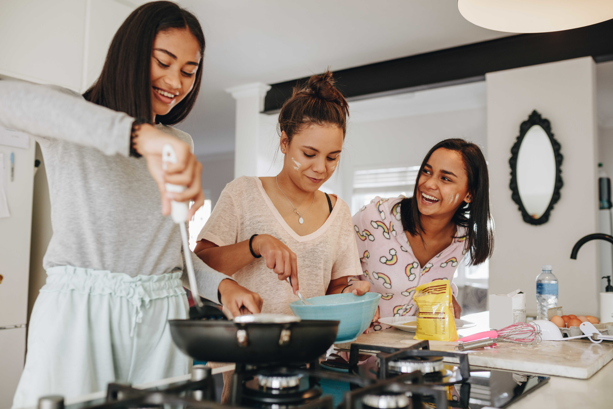 3 teenage girls smiling and cooking on the stovetop