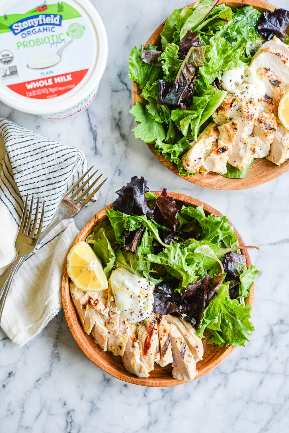 lemon pepper yogurt grilled chicken sliced and served in a bowl on top of mixed greens