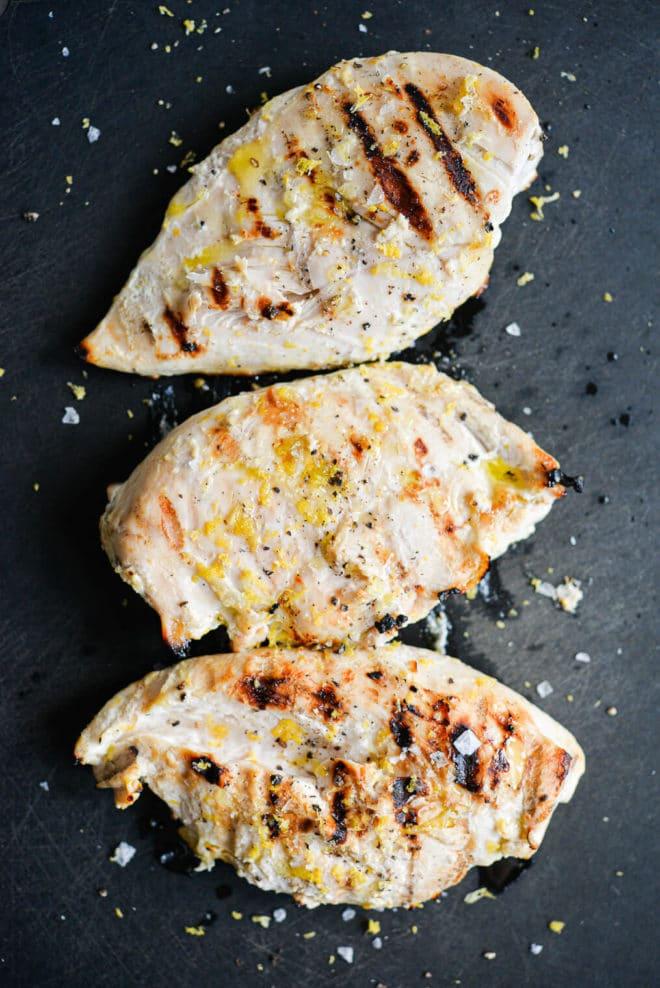 three grilled lemon yogurt chicken breasts resting on a black cutting board