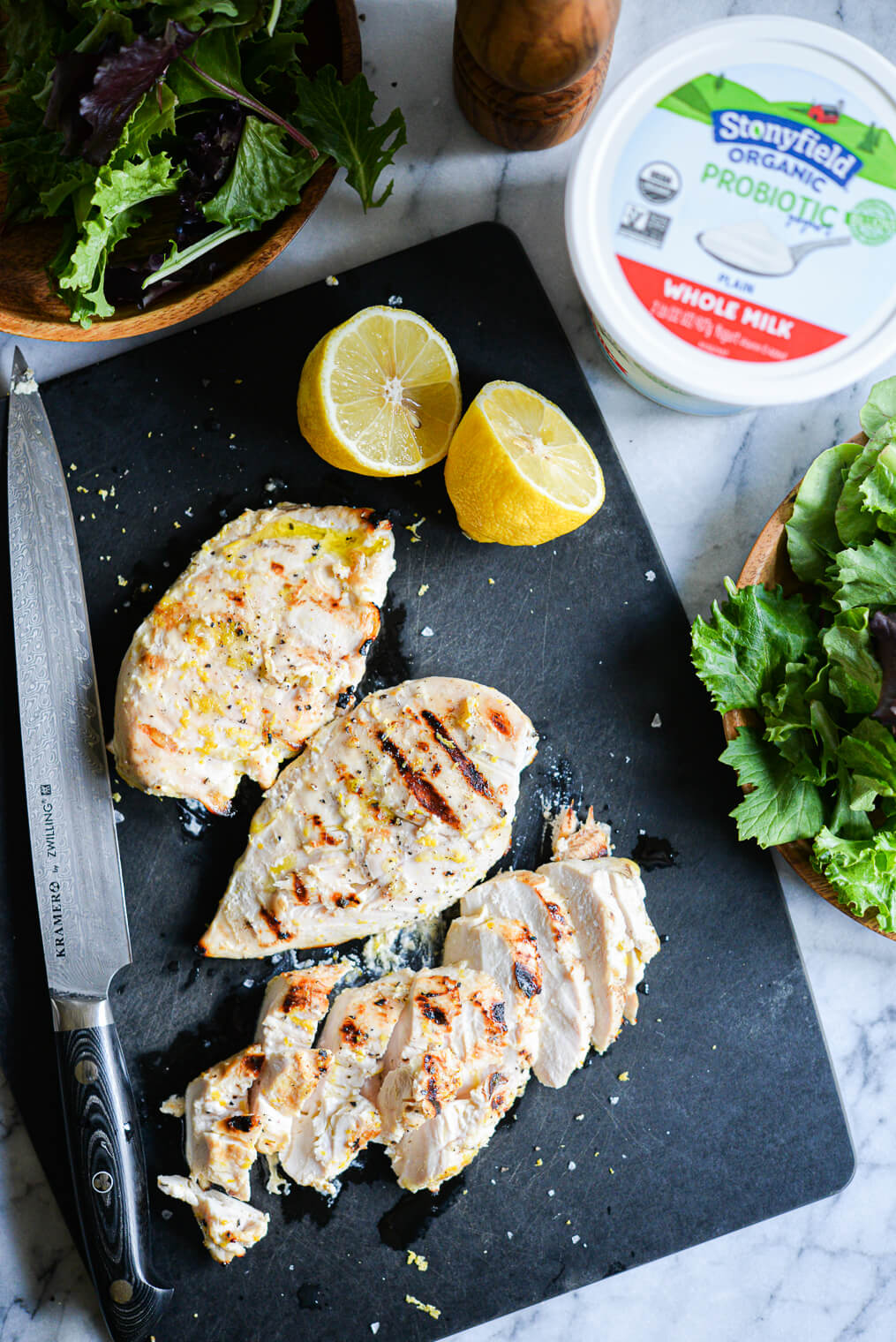 three lemon pepper yogurt grilled chicken breasts on a black cutting board next to a tub of plain yogurt and a halved lemon