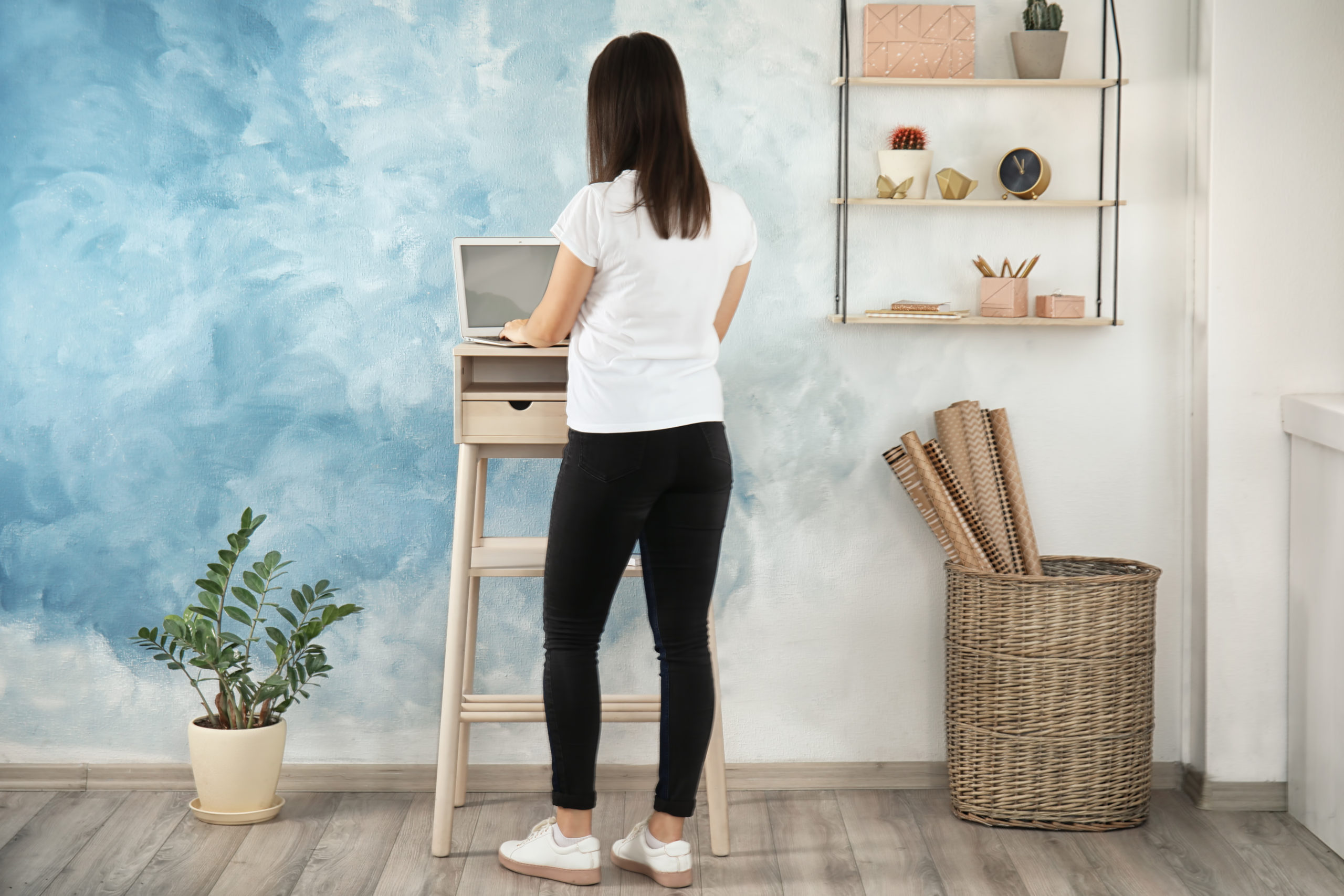 woman working at a standing desk against a blue wall