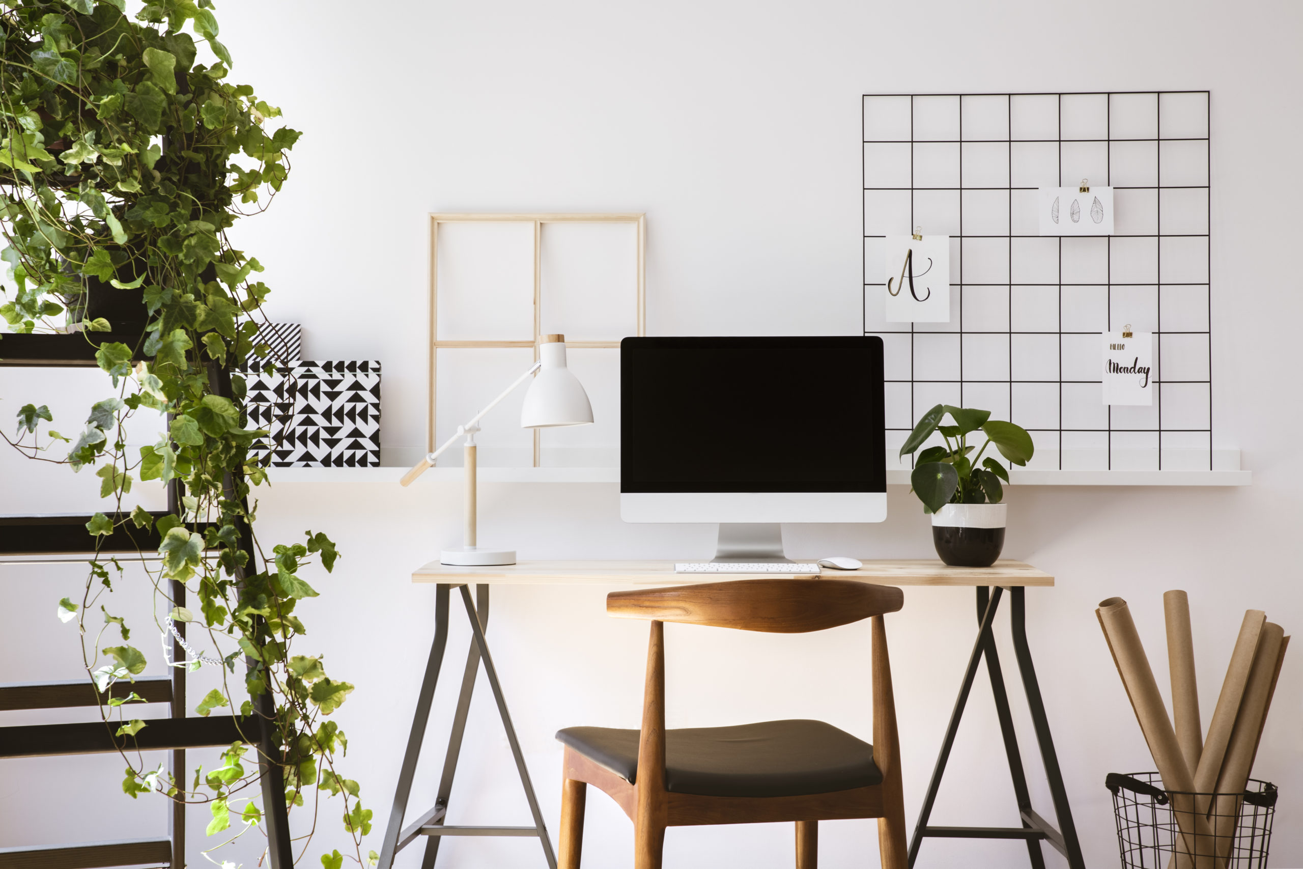 office with a white desk, mac monitor, wooden chair, and a shelf with a plant on it
