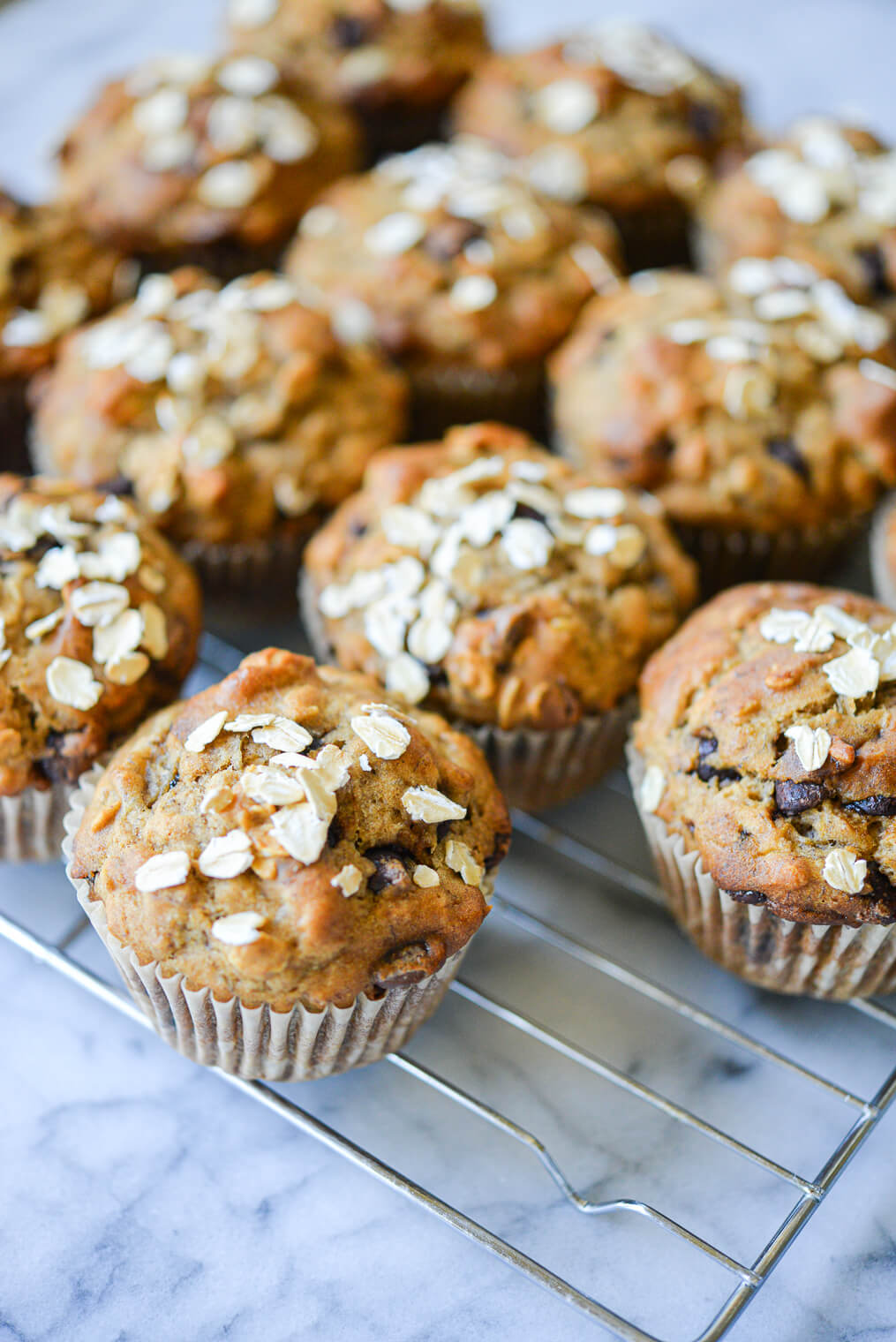 side angle view of chocolate chip banana oat muffins on a wire rack on a marble ssurface