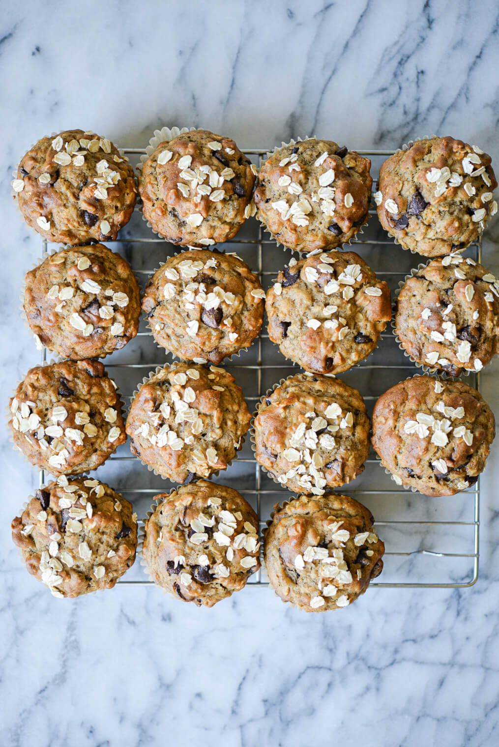 chocolate chip banana oat muffins on a wire baking rack on a marble surface