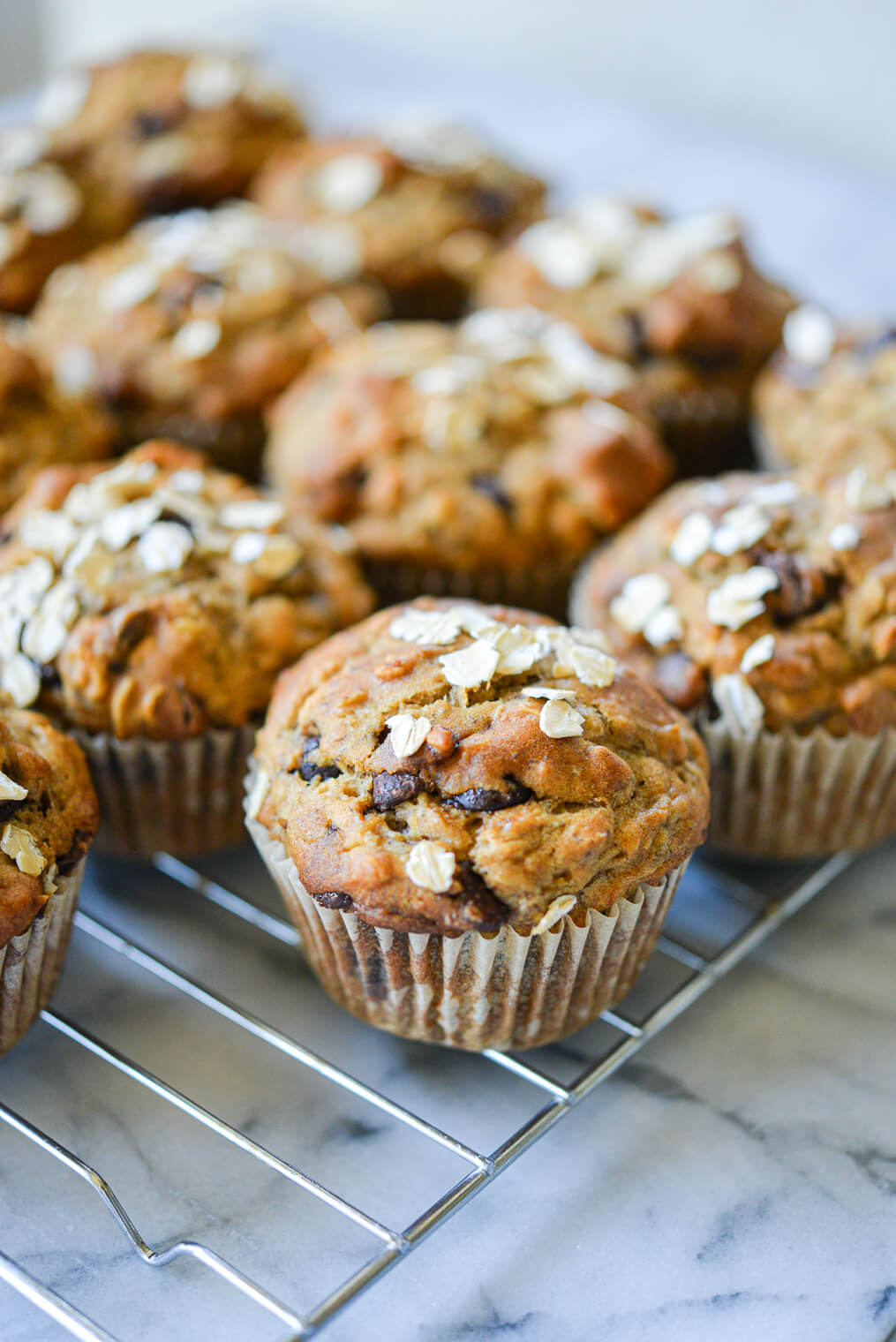 side angle view of chocolate chip banana oat muffins on a wire rack on a marble surface