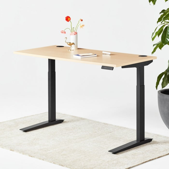 a black and wood standing desk with a vase of flowers on it
