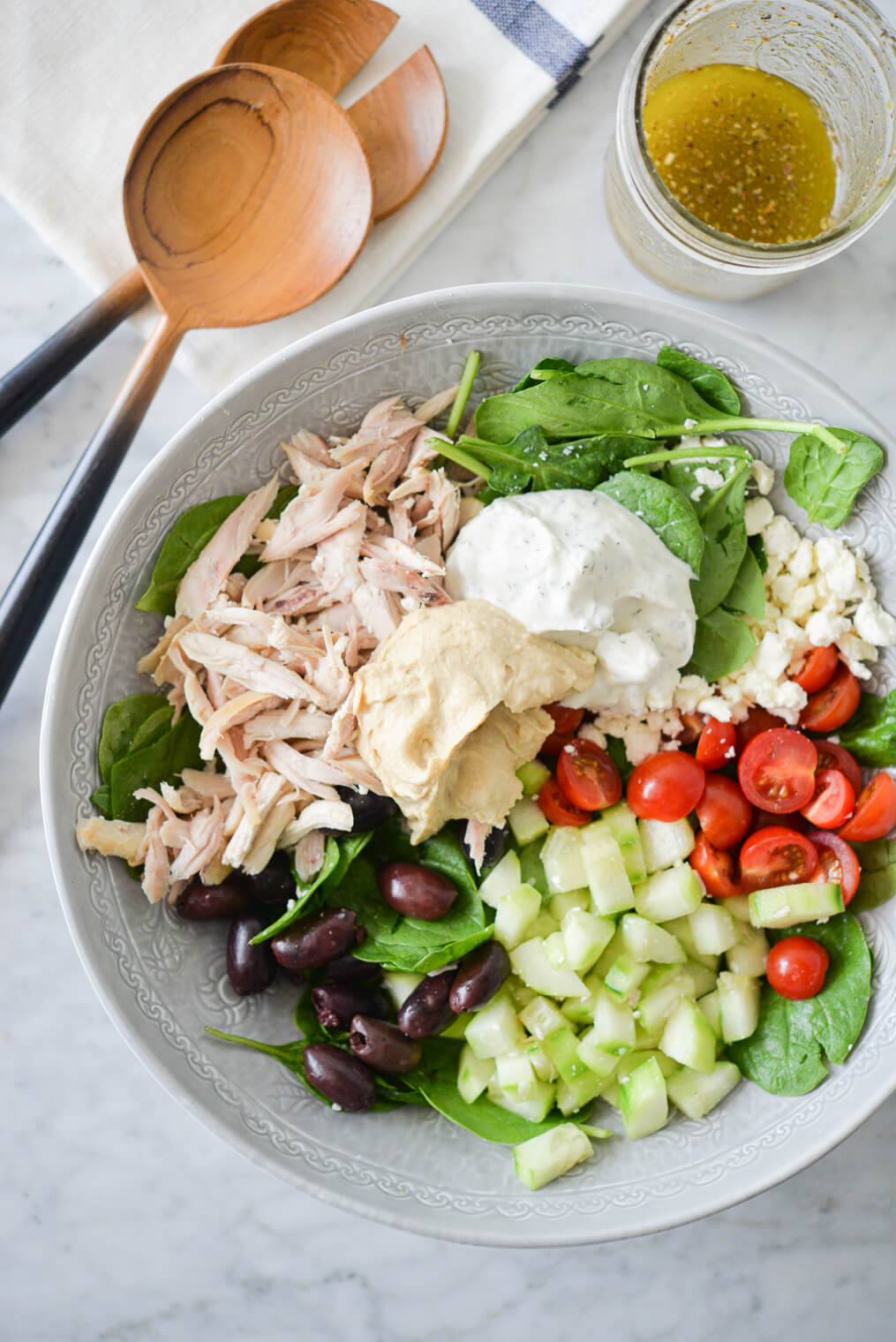 a bed of spinach topped with halved tomatoes, feta cheese, cucumbers, olives, shredded chicken, hummus, and tzatziki sitting next to a jar of homemade greek dressing and two wooden serving spoons all on a marble surface