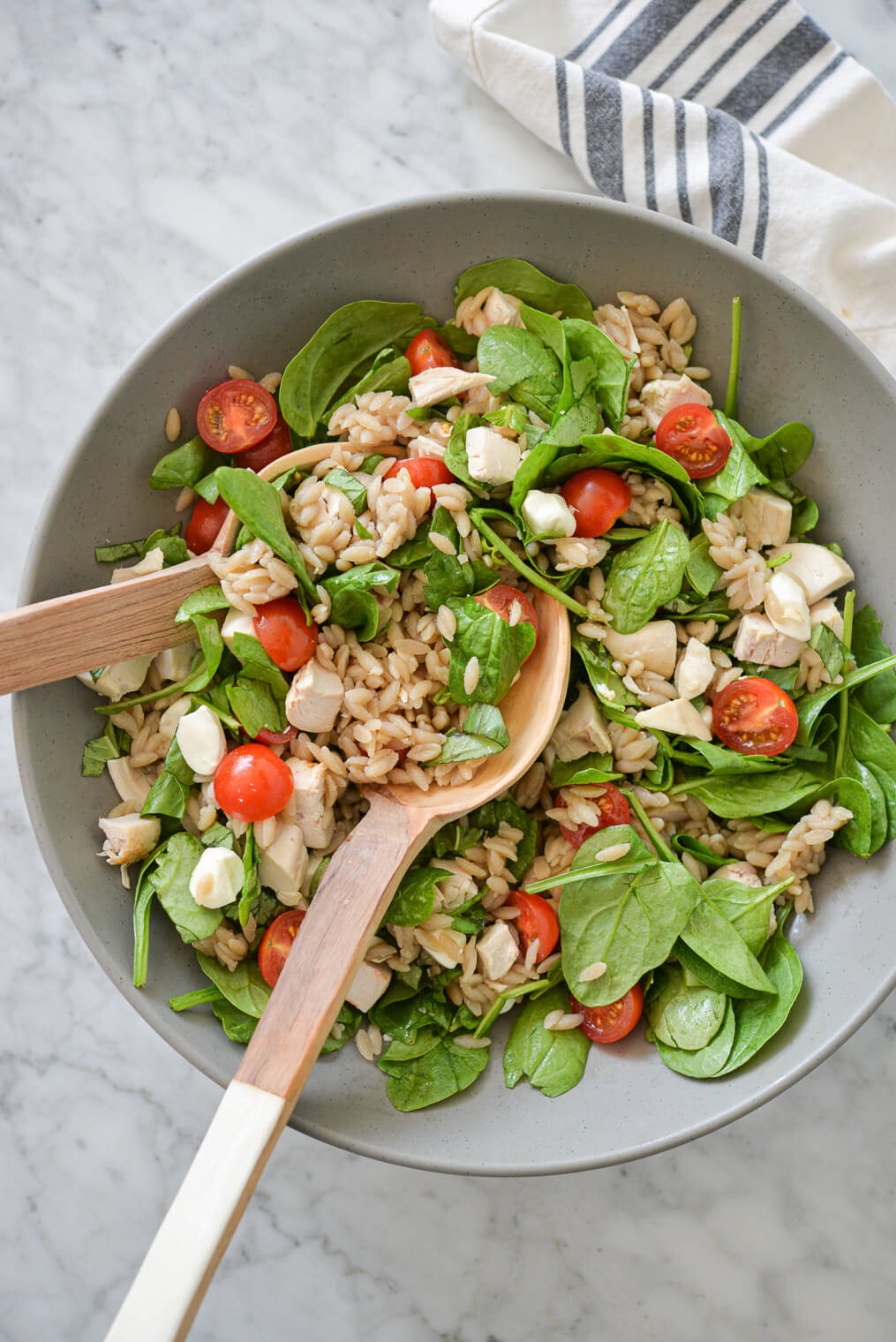 a large gray bowl filled with orzo, cherry tomatoes, spinach, mozzarella pearls, and chicken with two wooden serving spoons on a marble surface