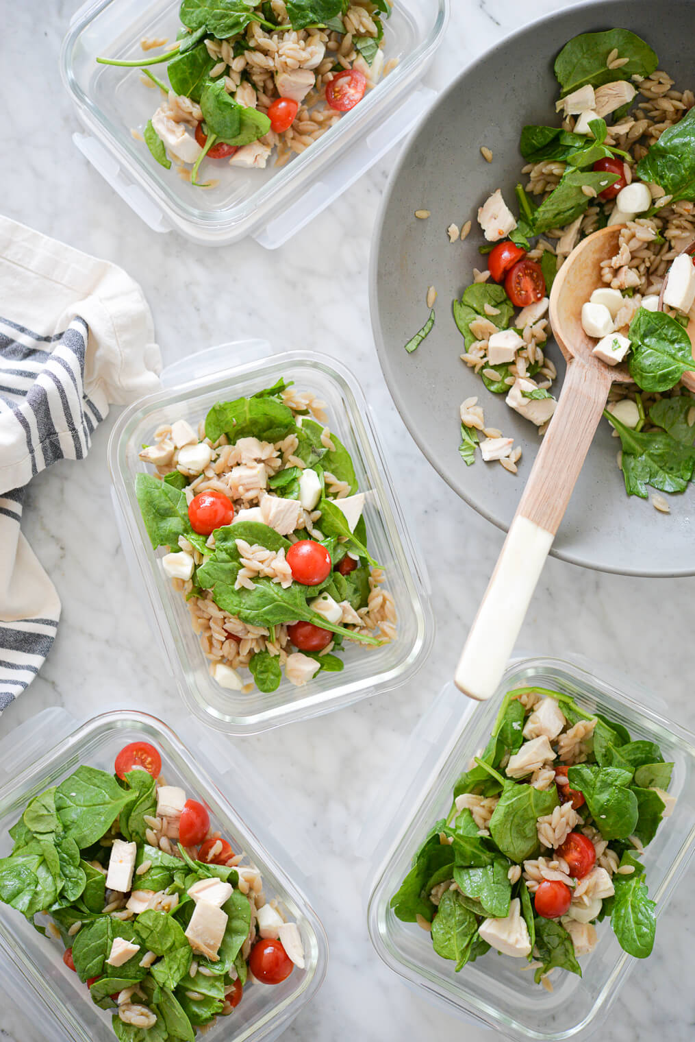 a large bowl of orzo caprese salad being split among smaller glass meal prep containers