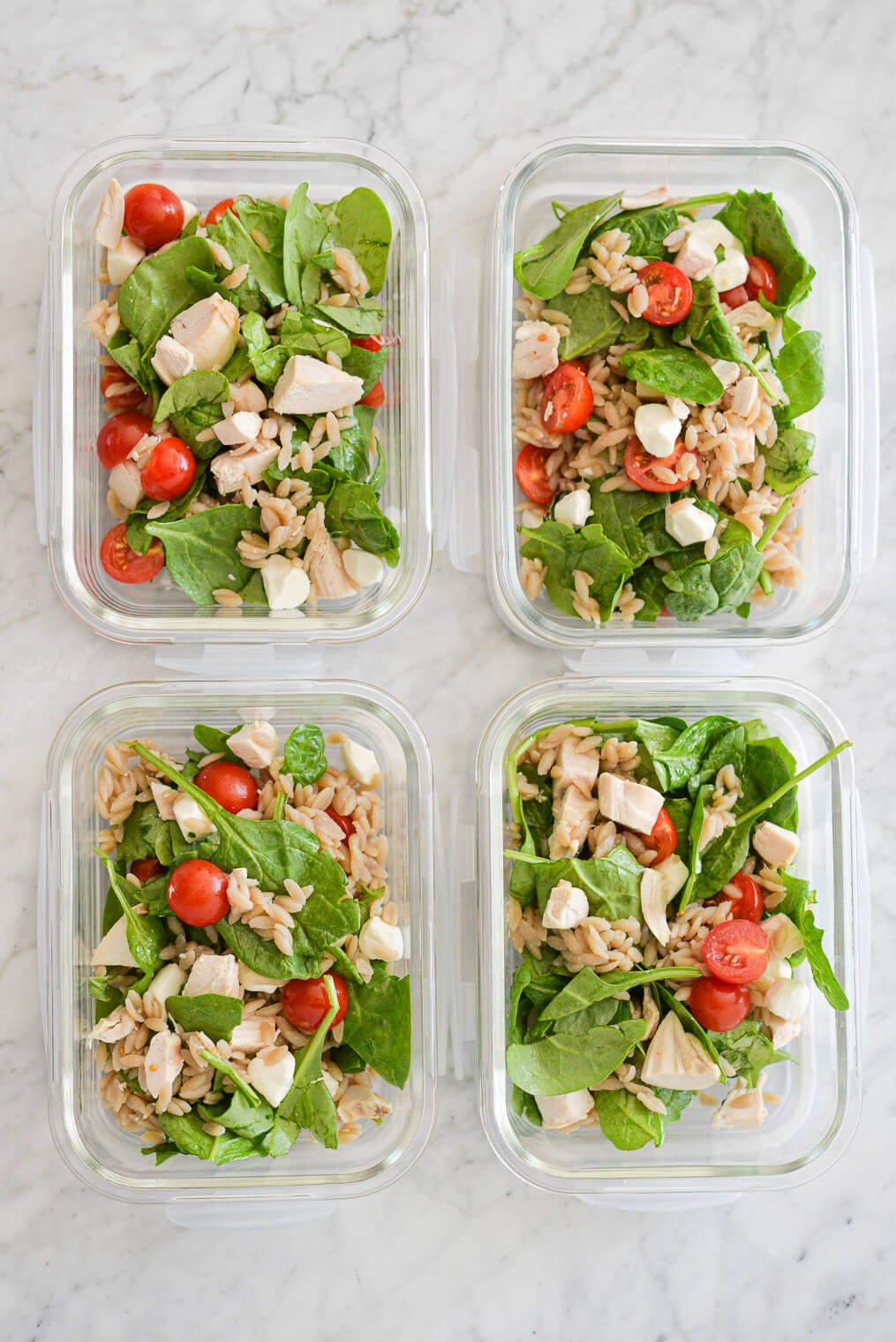 4 rectangular glass meal prep containers filled with orzo caprese salad sitting on a marble surface