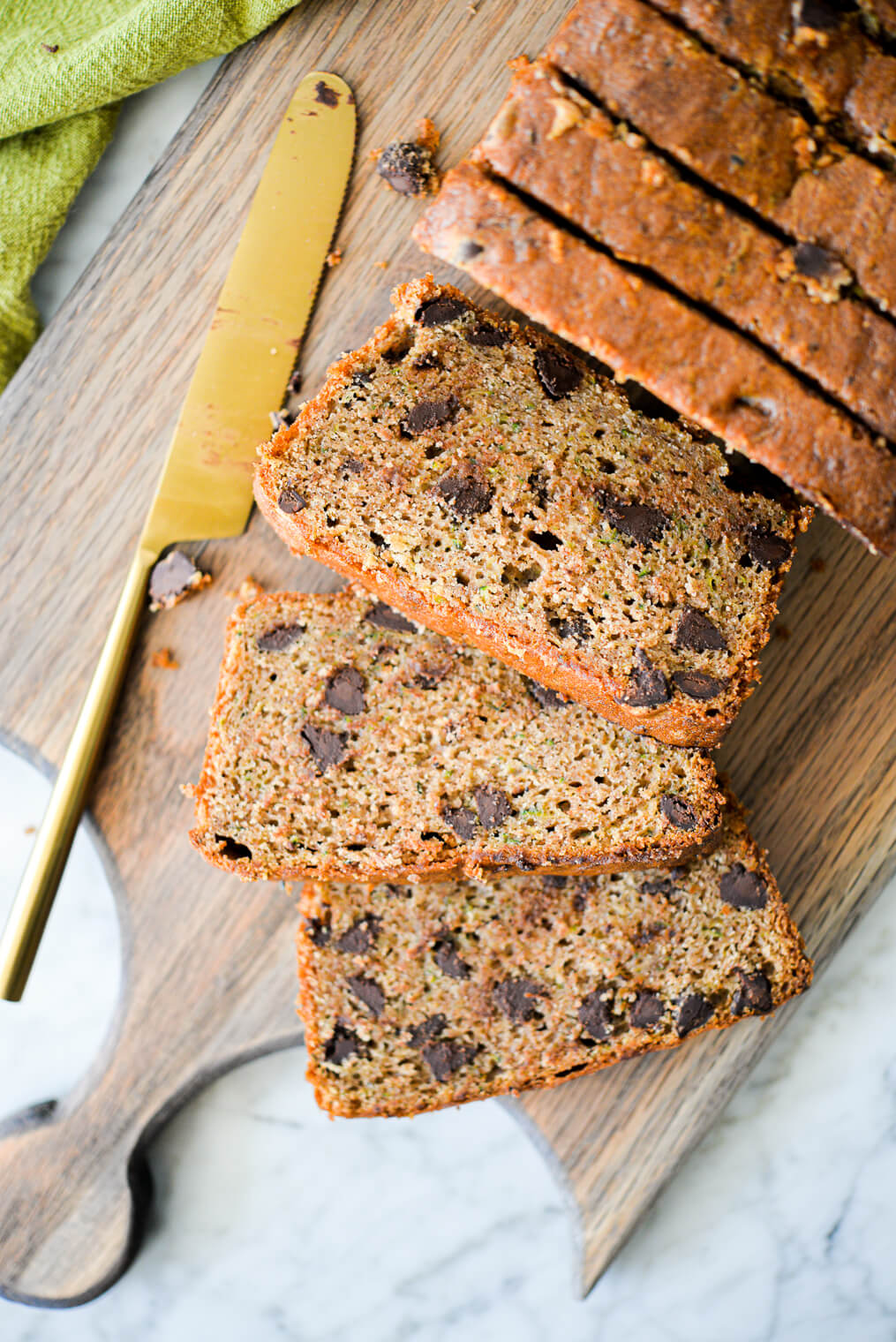 a batch of sliced chocolate chip zucchini bread laying on a wooden cutting board next to a brass butter knife on a marble surface