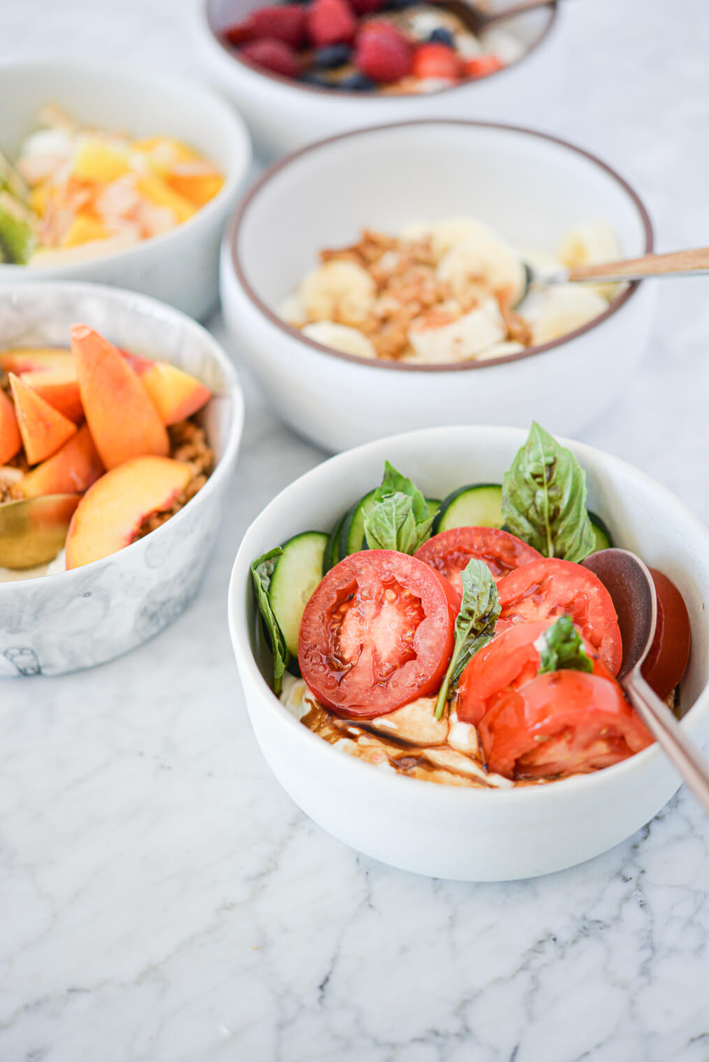 a white bowl filled with plain Greek yogurt, sliced cucumbers and tomatoes, fresh basil leaves, and balsamic vinegar surrounded by various other Greek yogurt bowls all sitting on a marble surface