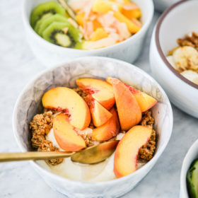 top view of a marble bowl with plain Greek yogurt, sliced fresh peaches, granola, and honey on a marble surface