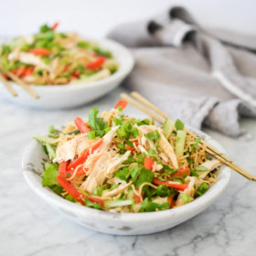 side view of sesame noodles with raw strips of cucumber, red bell peppers, and snap peas in a stone bowl with gold chopsticks resting on the rim all on a marble surface
