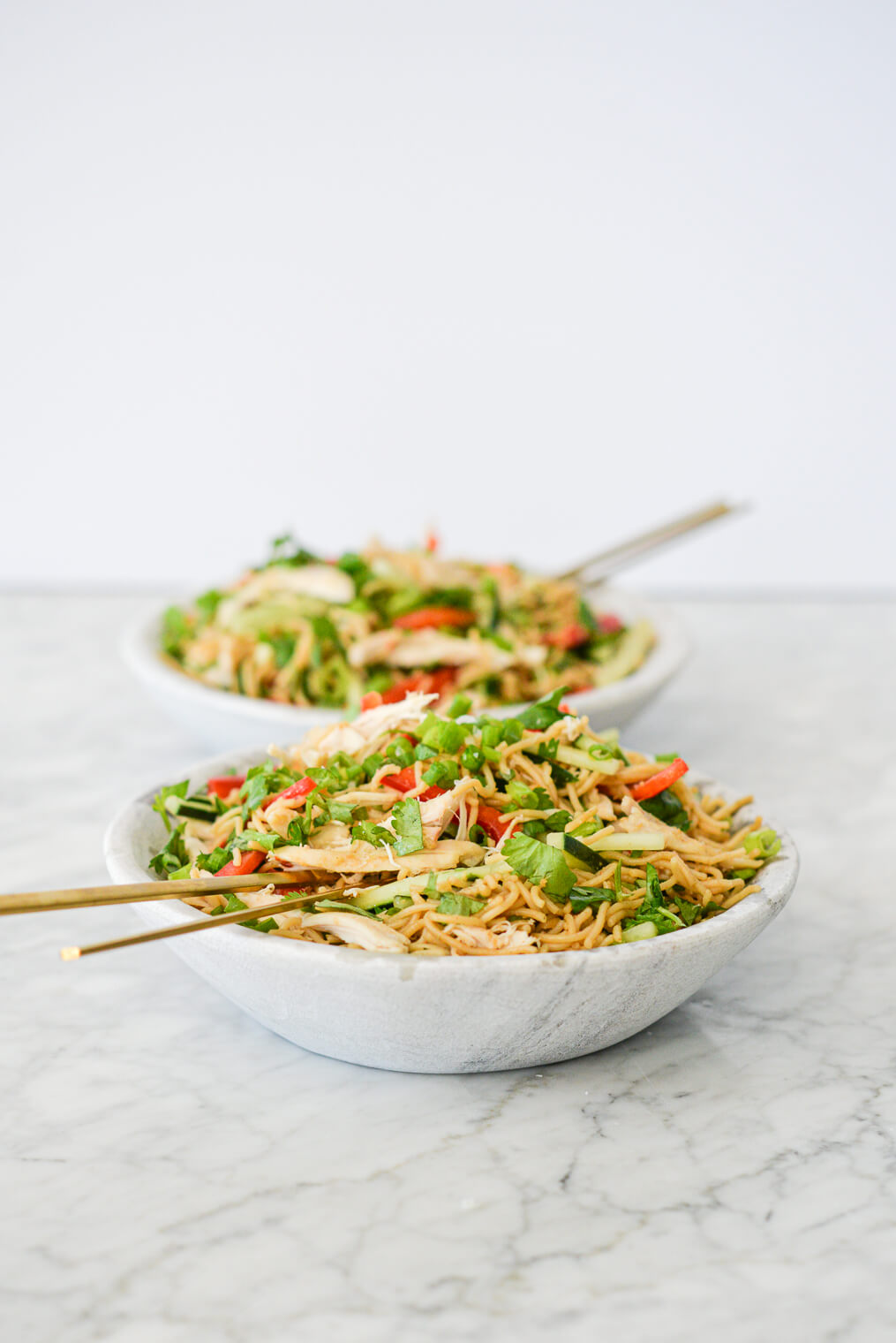 side view of two bowls of sesame noodles with raw strips of cucumber, red bell peppers, and snap peas in a stone bowl with gold chopsticks resting on the rim all on a marble surface