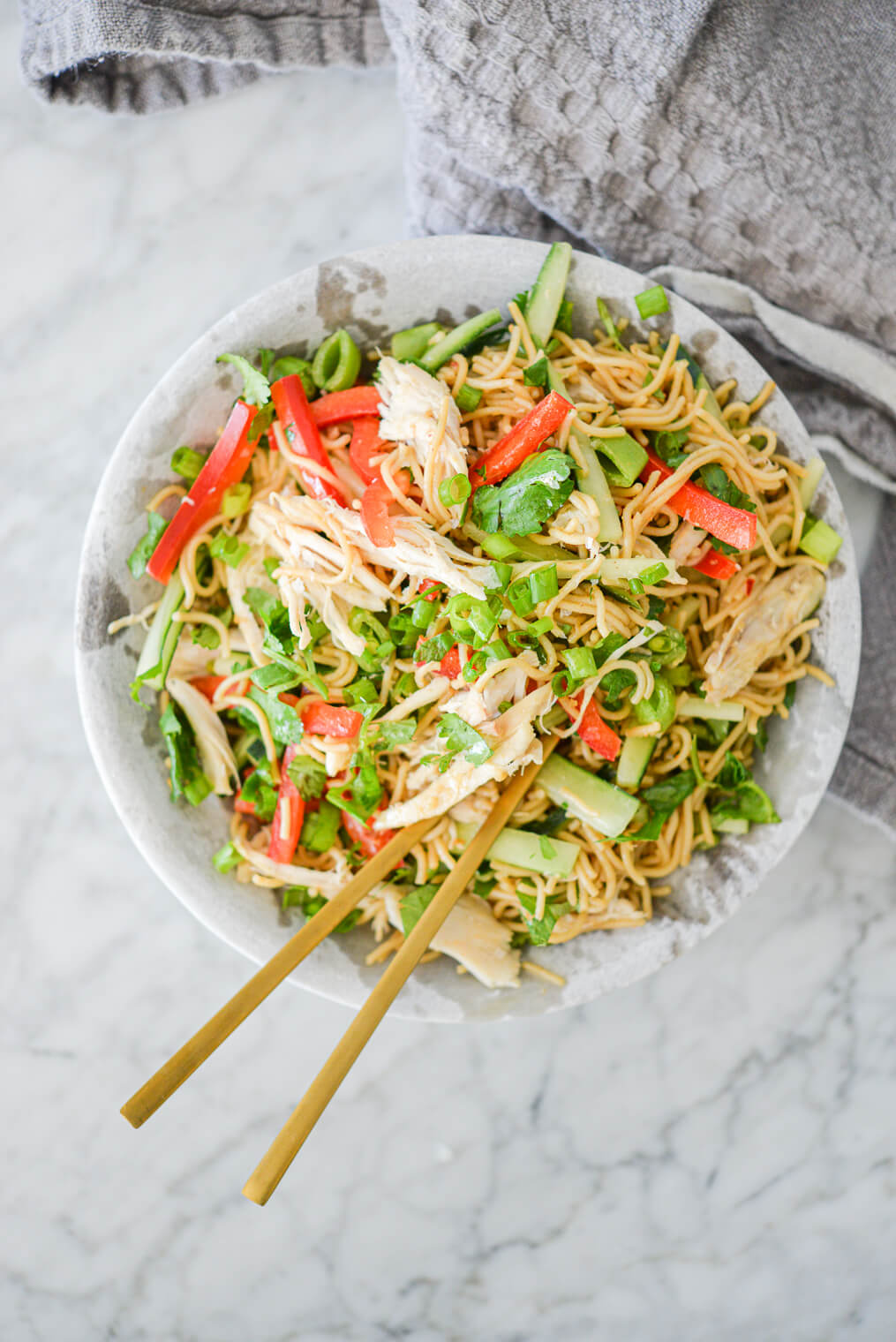 top view of sesame noodles with raw strips of cucumber, red bell peppers, and snap peas in a stone bowl with gold chopsticks resting on the rim all on a marble surface