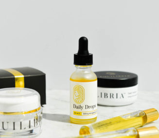 a glass bottle of equilibria cbd drops, rollers, relief cream, and softgels on a marble surface