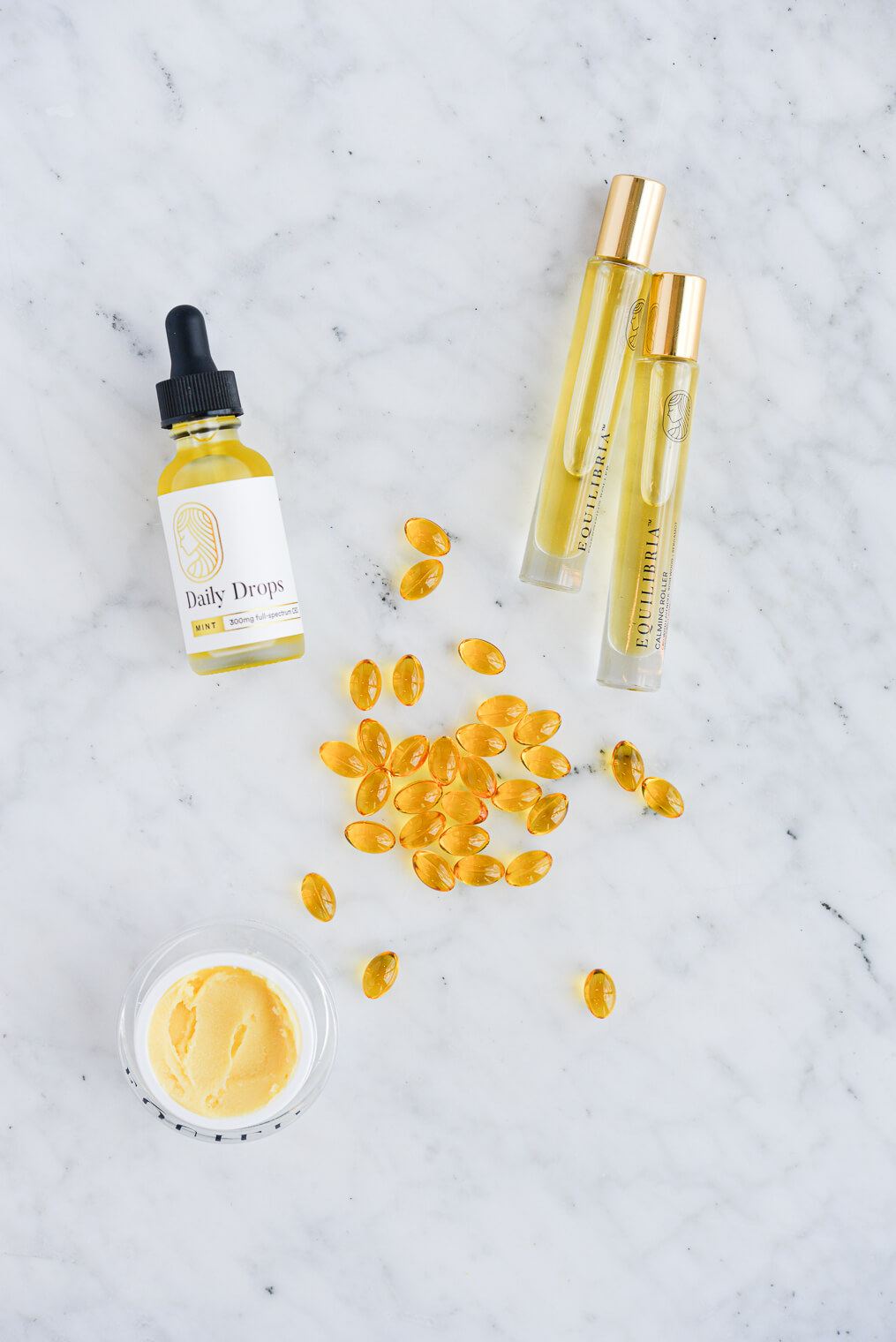 equilibria cbd drops, rollers, cream, and softgels on a marble surface