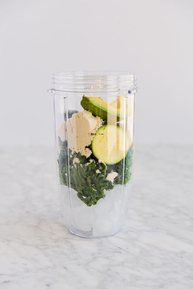 ingredients for green smoothies in an individual serving blender cup sitting on a marble surface