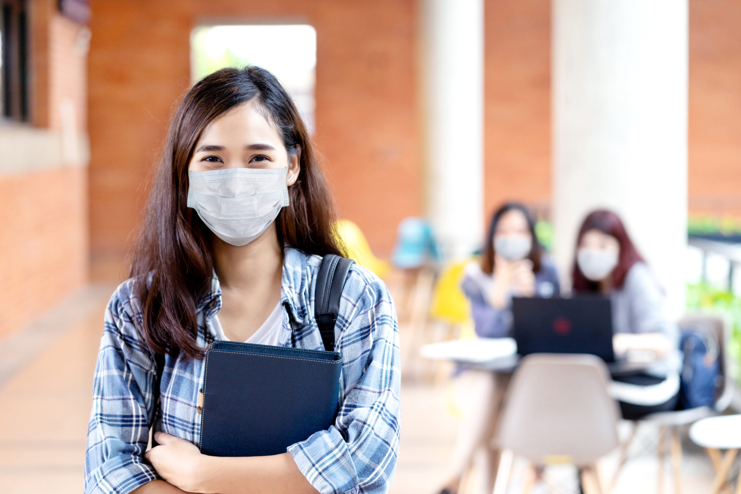 Portrait of young asian student wear mask looking at camera holding notebook or tablet in arm in concept come back or return to school, school reopening and unlock after covid or coronavirus outbreak.