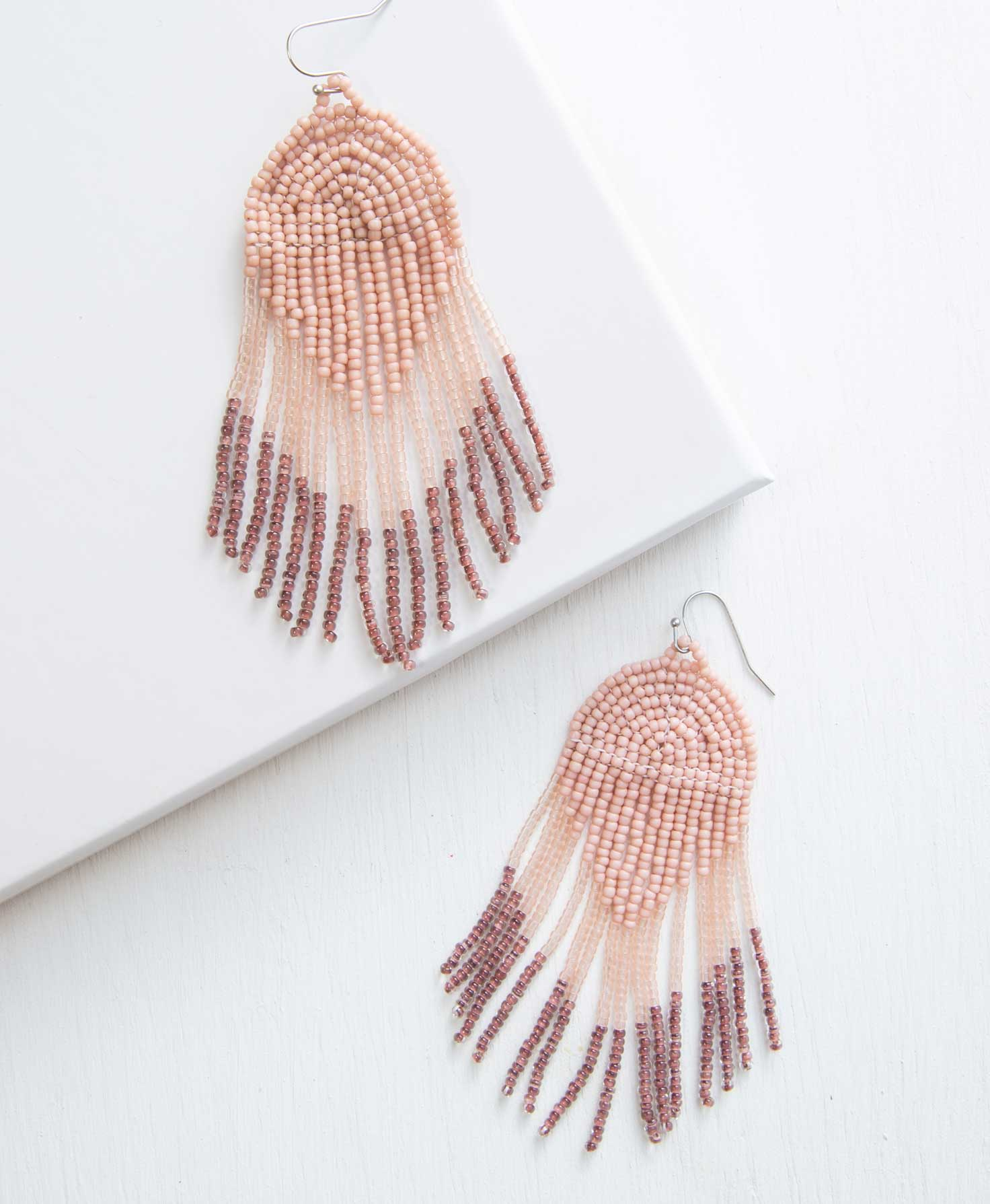 beaded pink earrings on a white surface