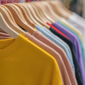 multiple colors of tshirts hanging on wooden hangers on a rack