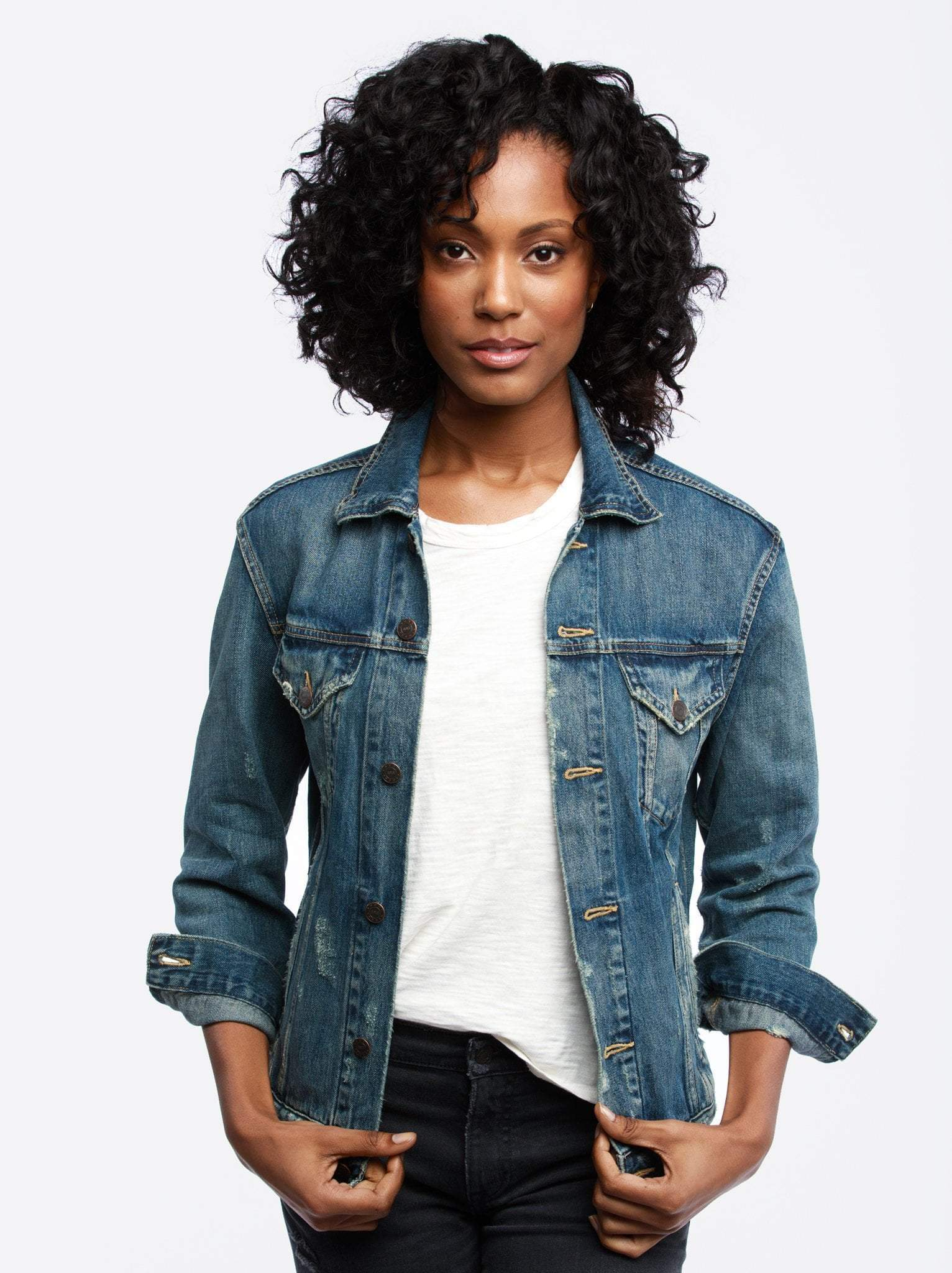 black woman with curly hair in a denim jacket, white tshirt, and black jeans