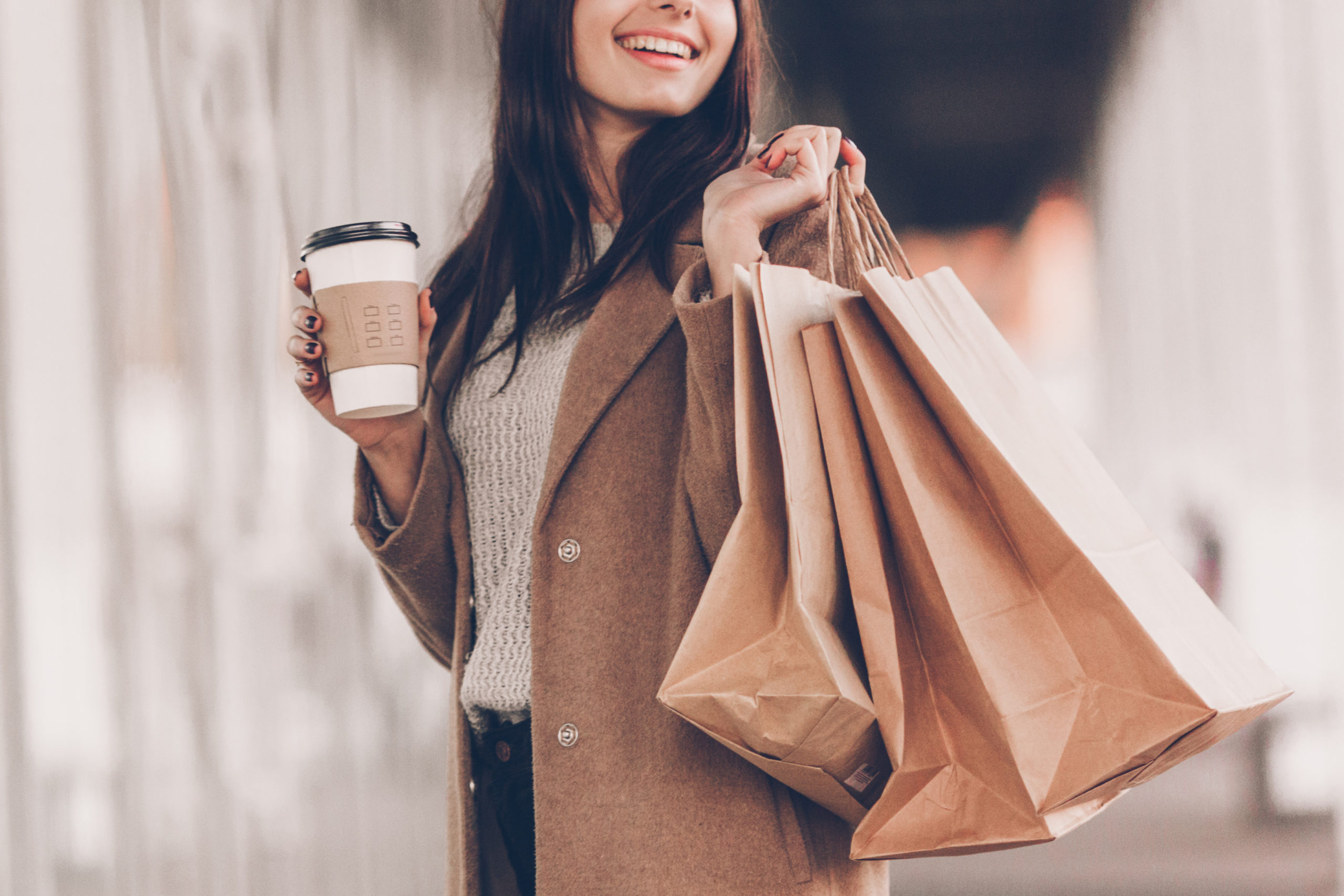 woman with brown hair wearing a coat and sweater with a cup of to-go coffee and shopping bags