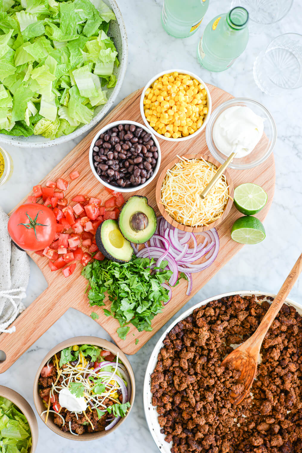 wooden cutting board on a marble surface topped with bowls of sour cream, shredded cheese, black beans, corn, diced tomatoes, cilantro, avocado, and red onion, next to a pan of ground beef