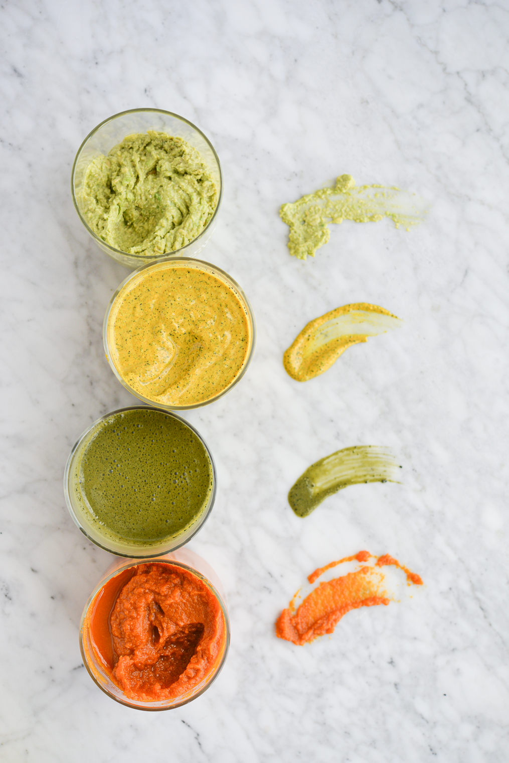 4 homemade face masks - light green, bright yellow, dark green, and orange - lined up in a row with smears beside them on a marble surface
