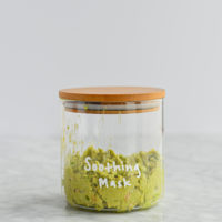 mashed avocado and oat mask in a glass jar with a wooden lid with soothing mask written on it in white letters on a marble surface