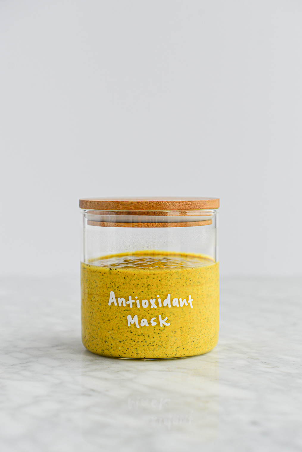 bright yellow turmeric and yogurt face mask in a glass jar with a wooden lid with the words 'antioxidant mask' written in white lettering