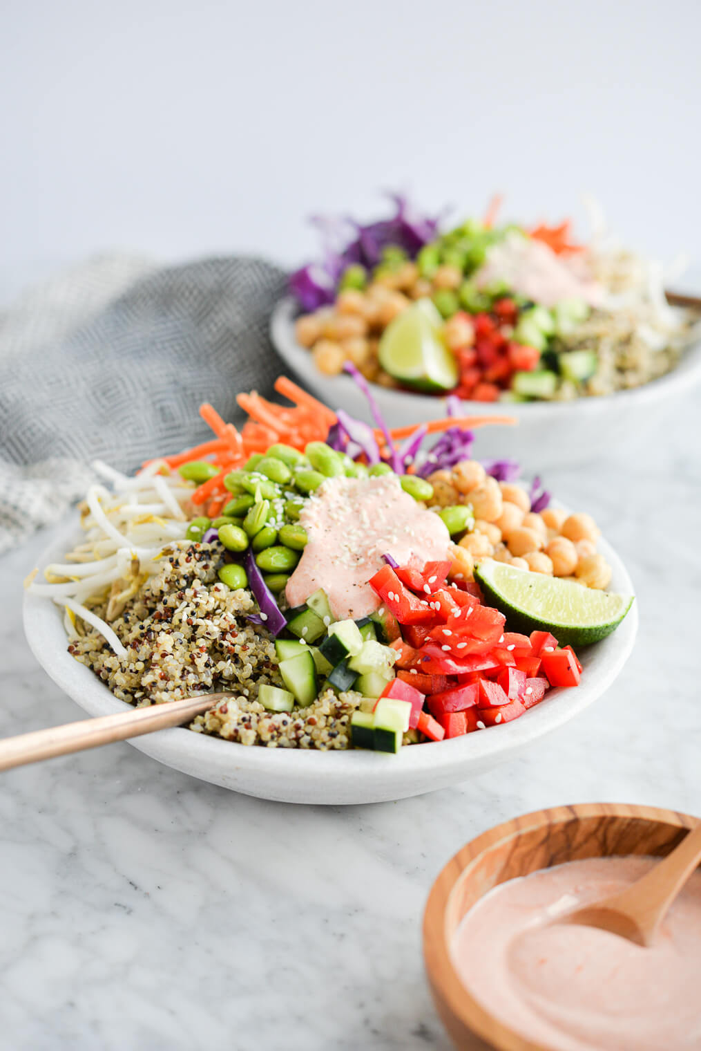 the side view of two thai red curry buddha bowls filled with quinoa, colorful veggies, and a creamy red sauce sitting on a marble surface