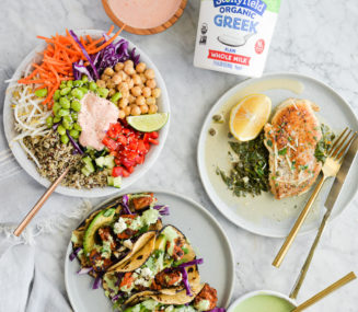 the top view of a thai red curry buddha bowl, three shrimp tacos, and a plate of creamy chicken piccata all surrounding a quart of Stonyfield's plain greek yogurt