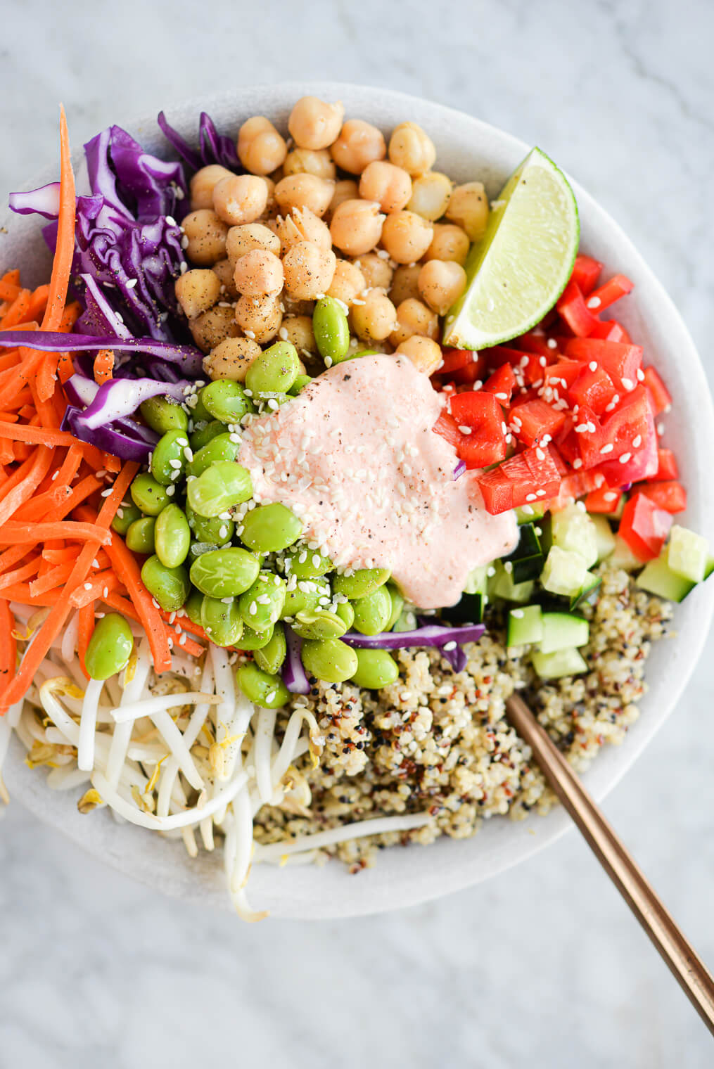 a close up of a thai red curry buddha bowl filled with quinoa, colorful, raw veggies, and a dollop of creamy yogurt red curry sauce on top, all sitting on a marble surface
