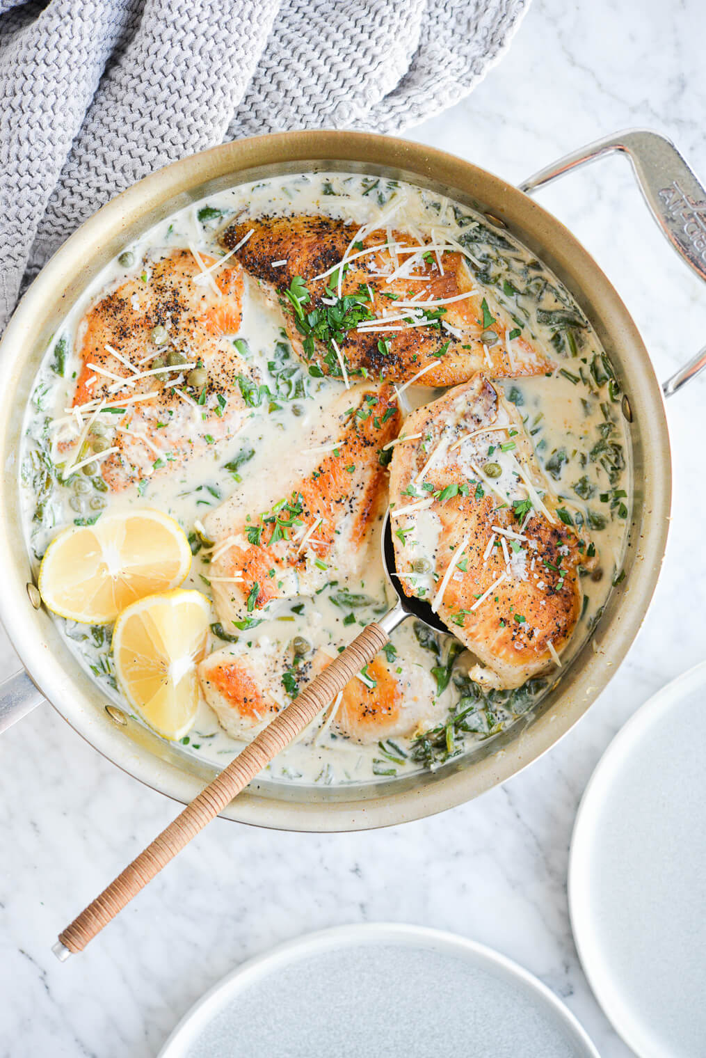 the top view of a skillet of creamy chicken piccata sprinkled with parmesan cheese on a marble surface