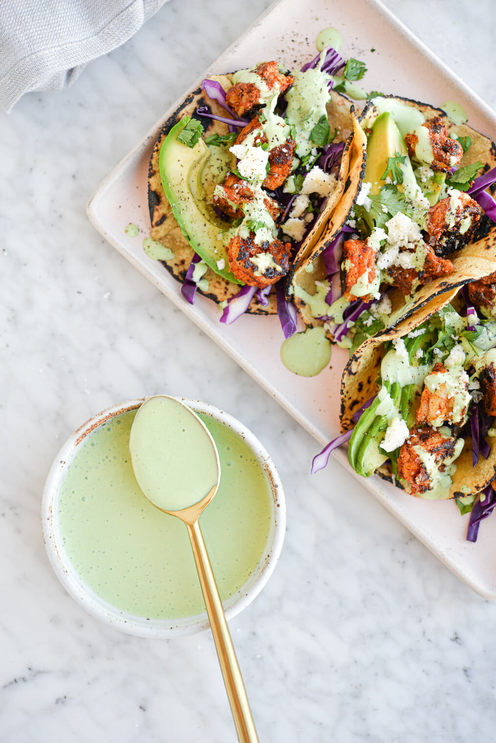 the top view of a platter of shrimp tacos (filled with seared shrimp, sliced avocado, red cabbage, and a creamy green yogurt sauce) sitting next to a bowl filled with more sauce all sitting on a marble surface