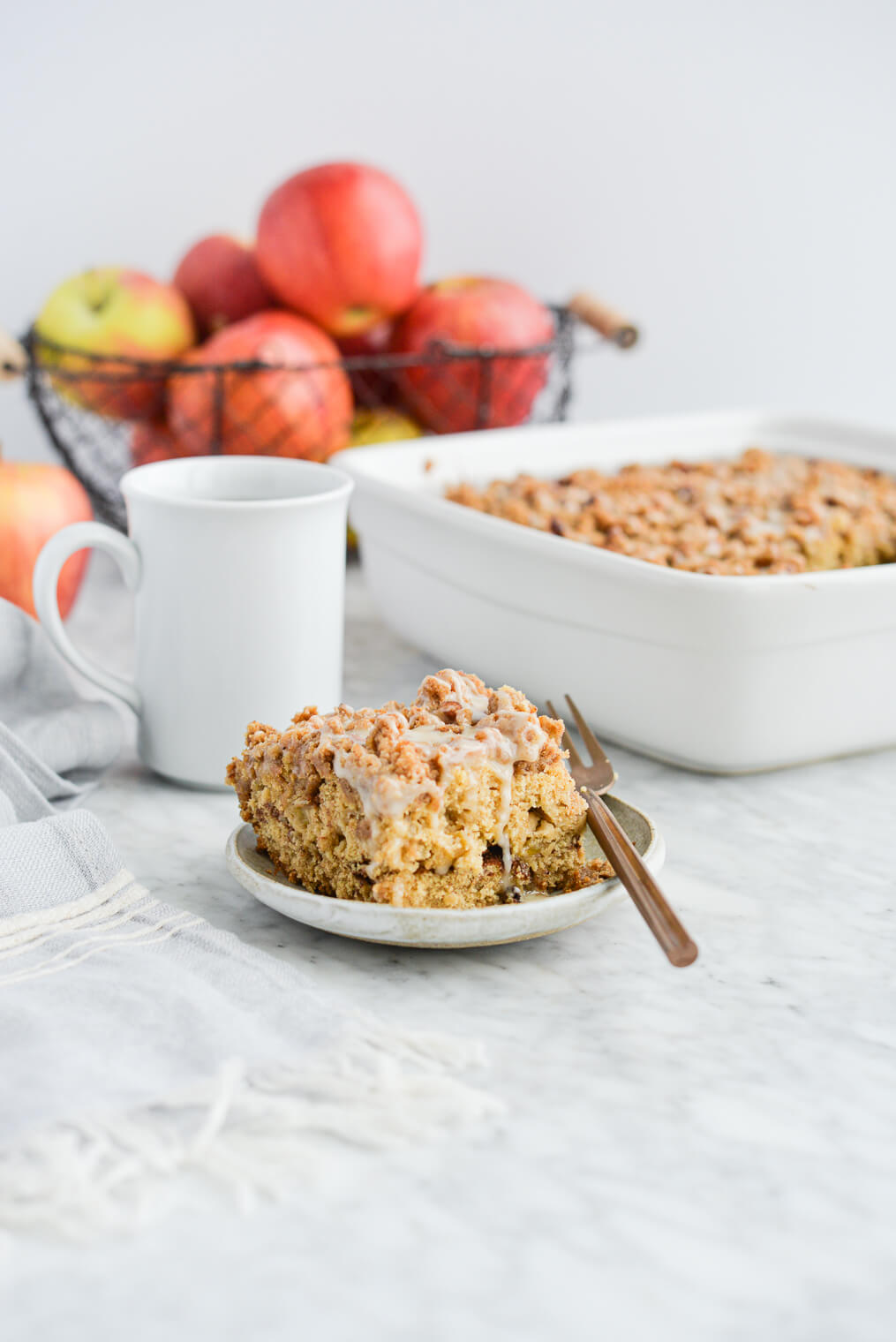the side view of a piece of apple coffee cake on a plate sitting next to the dish of coffee cake, a mug of black coffee, and a basket of apples