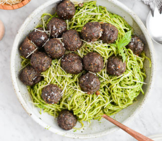 the top view of a bowl of pesto noodles topped with pesto meatballs sitting on a marble surface