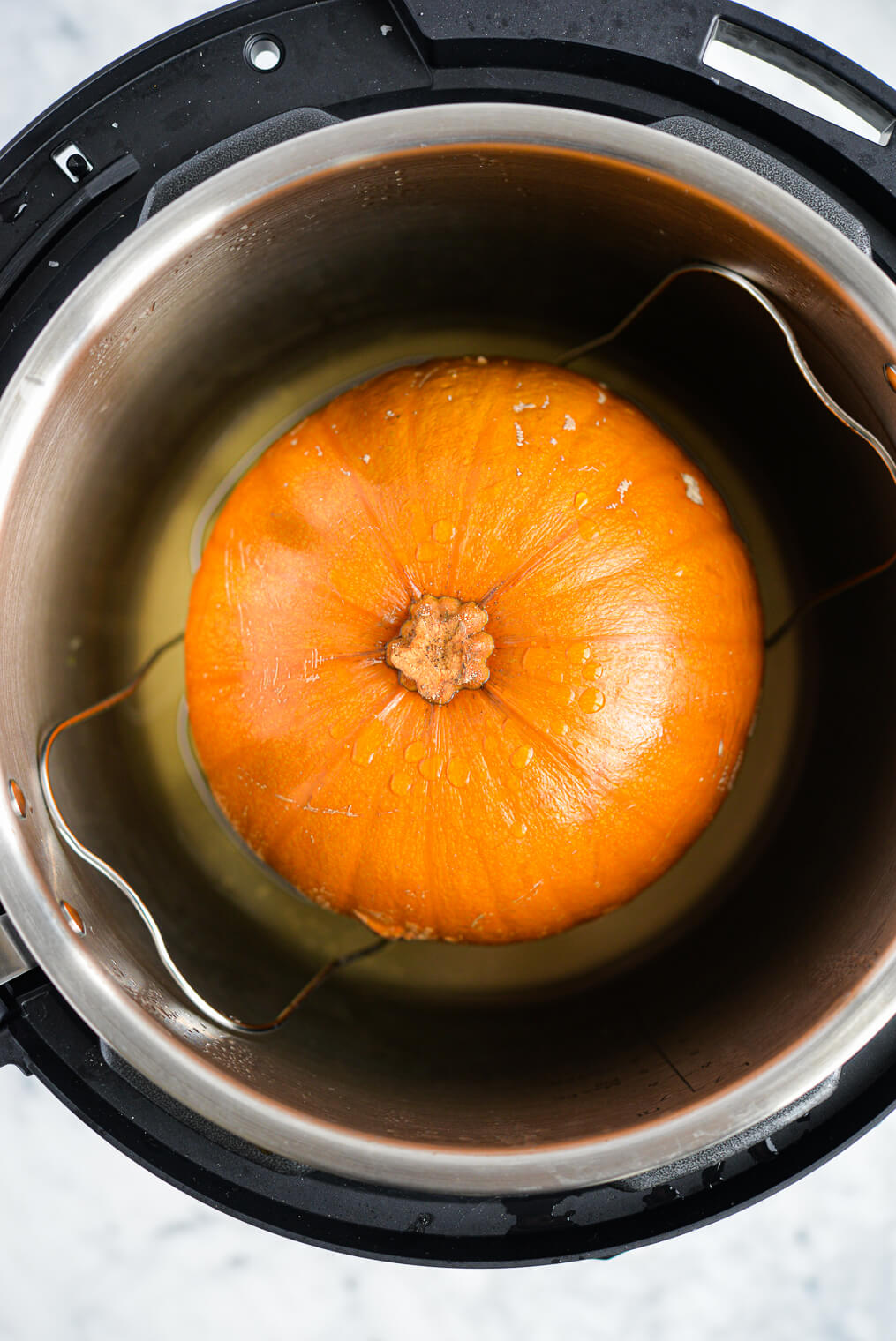 the top view of an open instant pot with a baking pumpkin sitting inside of it on the steamer grate, all on a marble surface