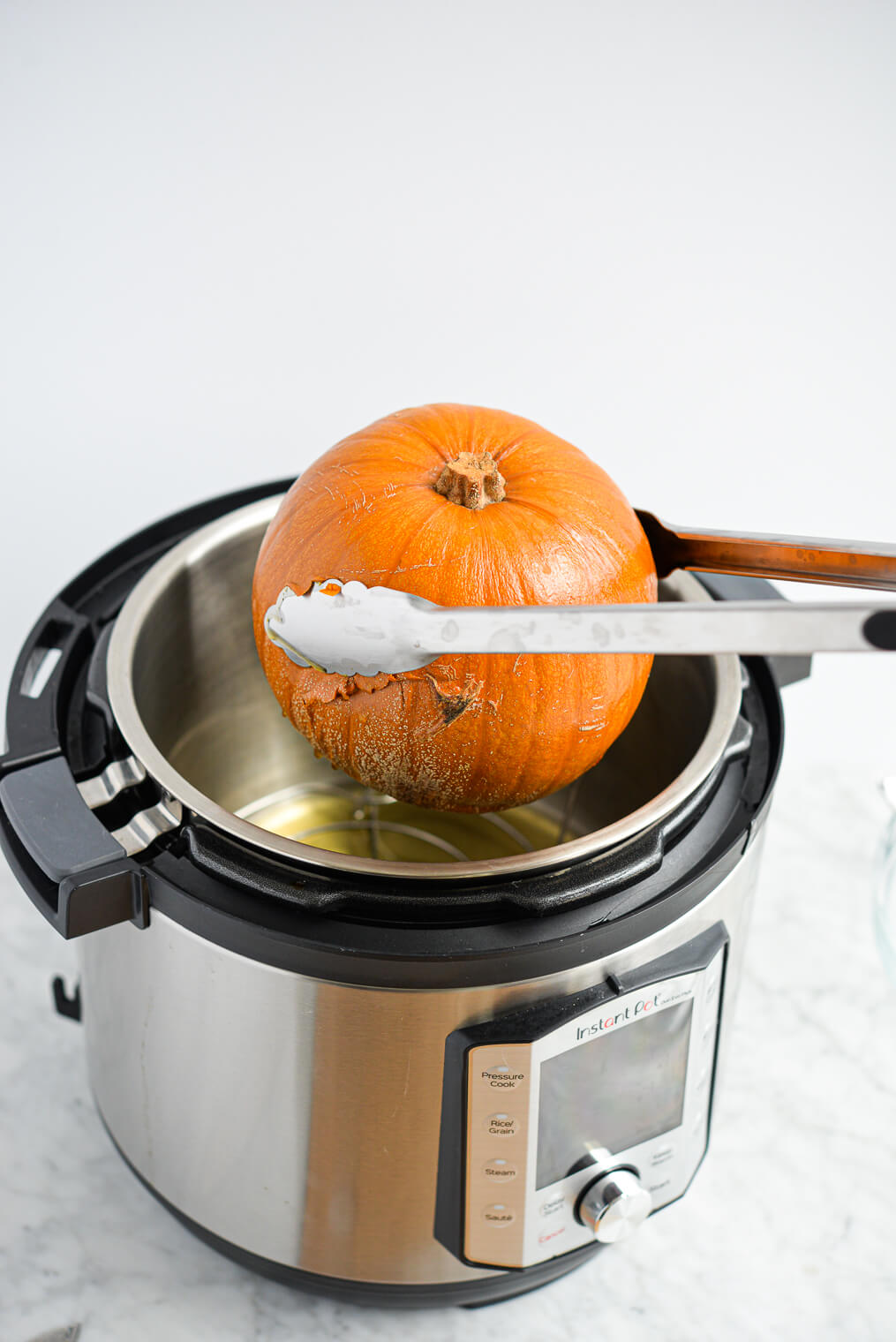 the side view of someone removing a cooked baking pumpkin from the instant pot using a pair of stainless tongs