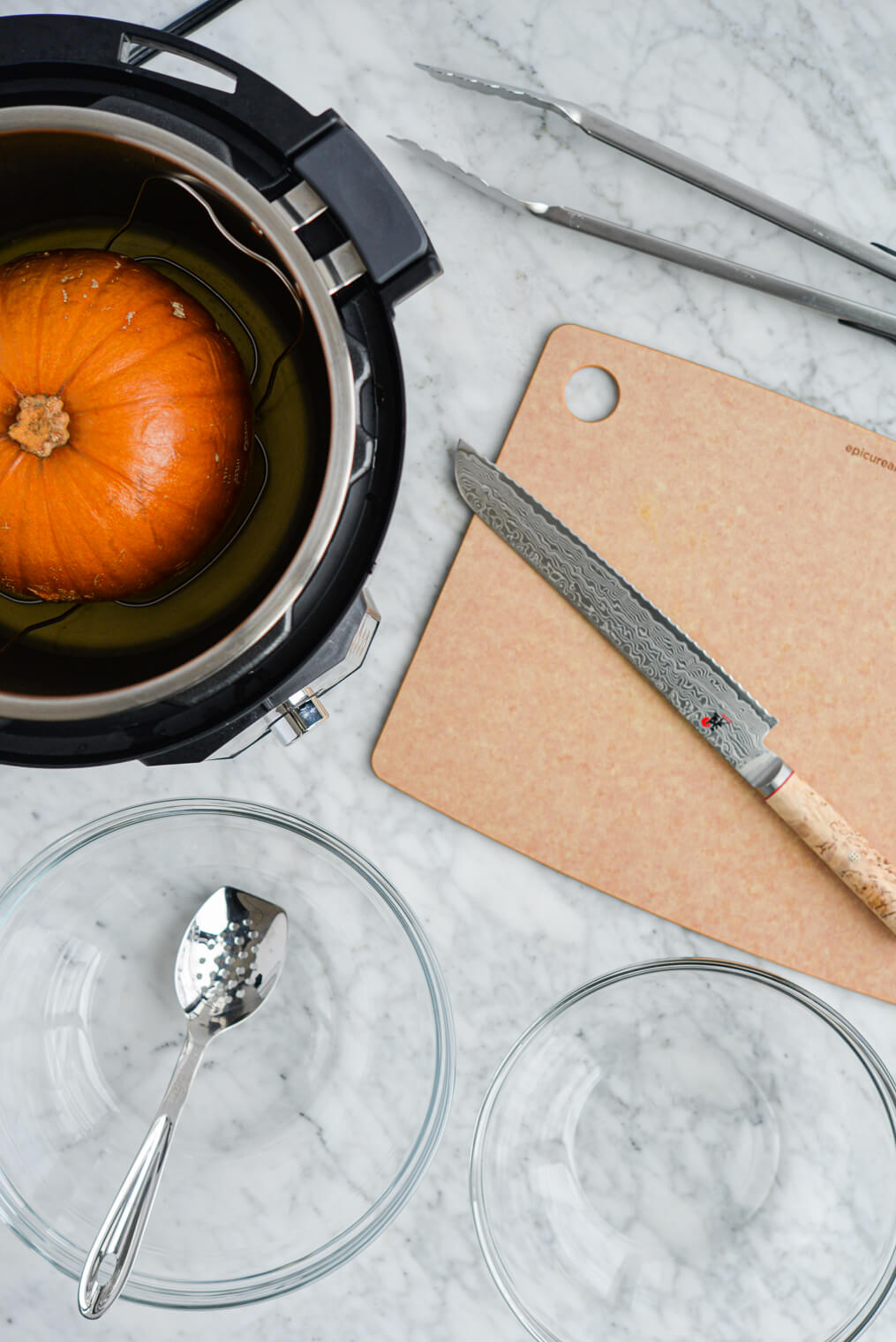 the top view of a baking pumpkin sitting in an open instant pot, a cutting board with a knife on top of it, two clear glass bowls, and one blunt-nose spoon, all sitting on a marble surface