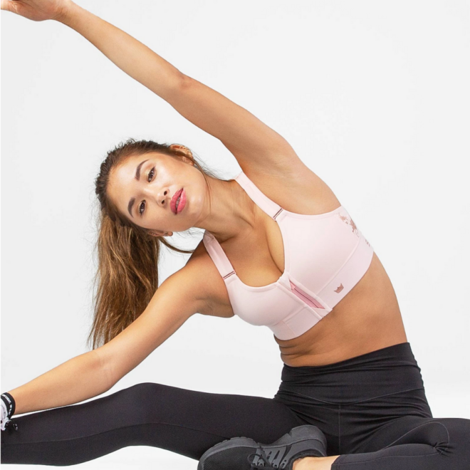 woman stretching while wearing the she fit flex sports bra