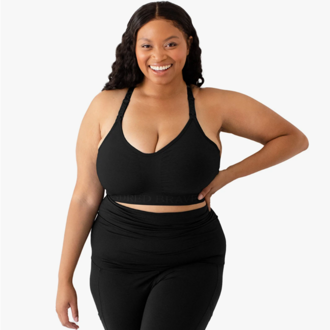 a woman standing and smiling at the camera wearing the kindred bravely sublime nursing bra and black pants
