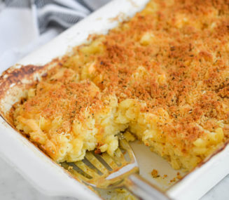 the side view of a casserole dish of oven-baked mac and cheese with one serving removed and a serving spoon scooping out another serving