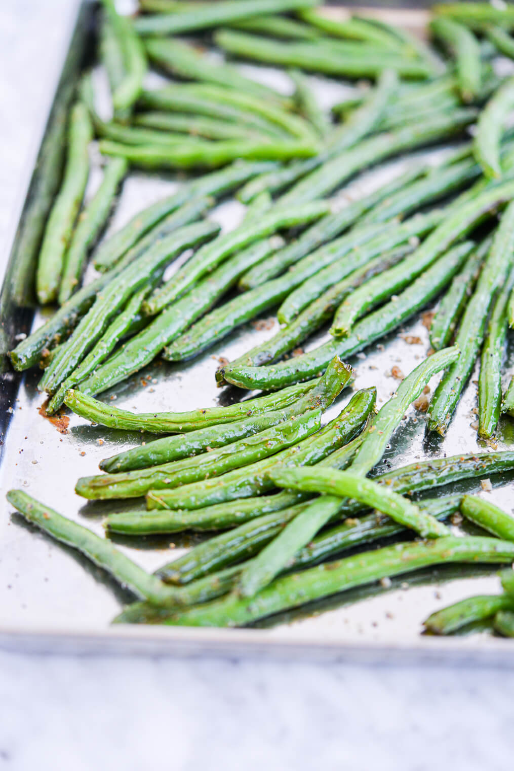 side view of roasted green beans on a sheet pan sitting on a marble surface