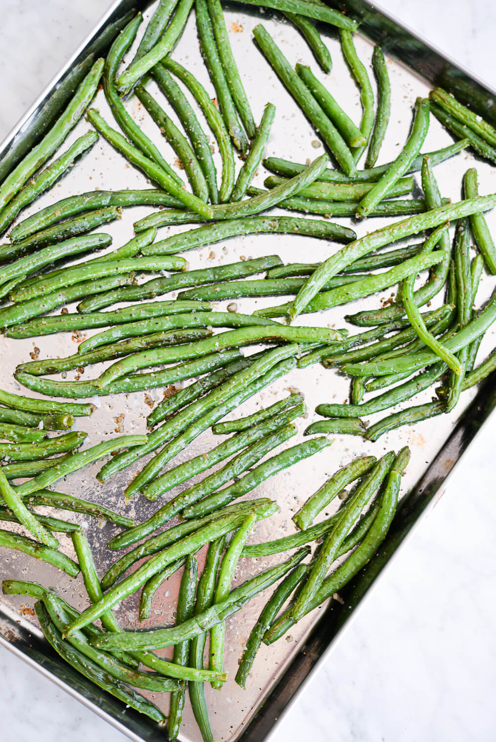 top view of roasted green beans on a sheet pan sitting on a marble surface