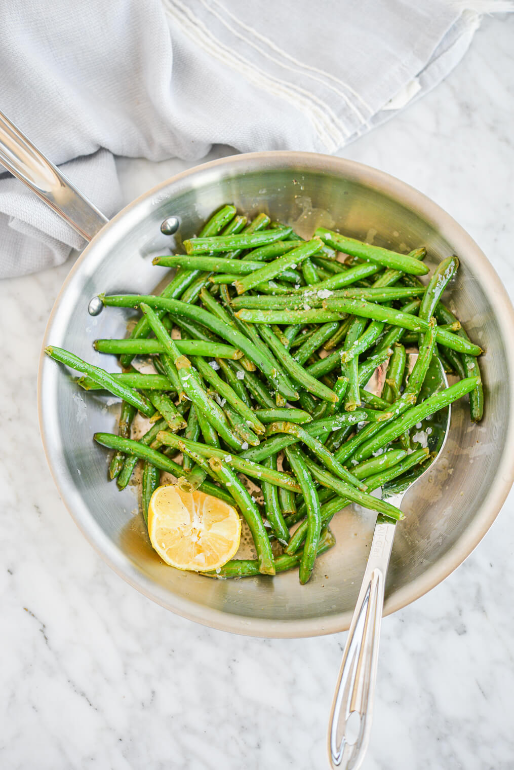 top view of bright green sauteed green beans in a stainless steel pan next to a lemon wedge