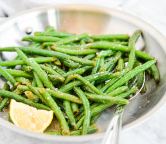 bright green sauteed green beans in a stainless steel pan next to a lemon wedge