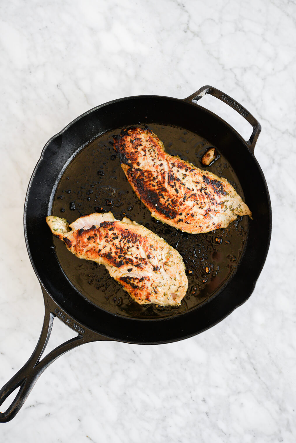 two seared turkey breast tenderloins in a cast iron skillet